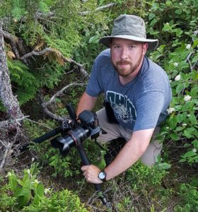 """Photograph of Andrew Lane Gibson """"The Buckeye Botanist"""" in the field with his camera."""